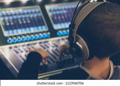 Little DJ adjusting sound switches on audio mixer in music studio.