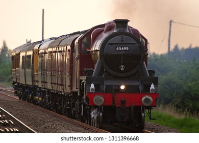 LITTLE DOWNHAM, CAMBRIDGESHIRE, UK - MAY 18, 2013: Catching the last of the sun's rays, LMS Jubilee Class 4-6-0 No. 45699 'Galatea' heads east through Little Downham, with the Carnforth to Kings Lynn.
