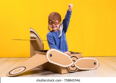 Little dreamer girl playing with a cardboard airplane. Childhood. Fantasy, imagination.