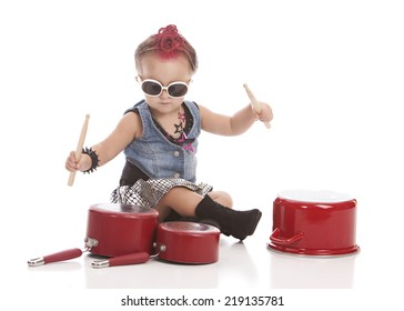 Little drummer girl.  Adorable toddler banging on pots and pans with drum sticks.  Isolated on white with room for your text.