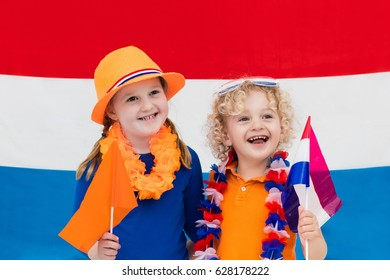 Little Dutch boy and girl wearing country symbols celebrating King day. Children support Holland sport team. Kids from the Netherlands. Young sport fans with national flag