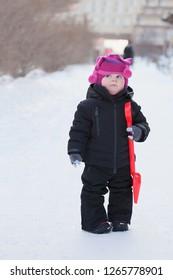 Little dvochka in black clothes. Little girl with a red shovel. Little girl in winter outside. Children's emotions. Mistrust. Red Hat. Black jumpsuit. Winter walk.