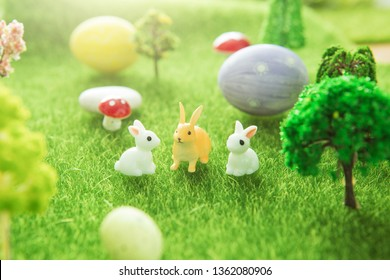 Little Easter bunny toys and Easter eggs on a green grass. Yellow easter egg spring meadow with a two white rabbit and easter eggs. Fairy tale