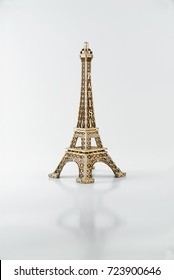 Little Eiffel tower on a white background. Souvenir. The memory of France. The Golden tower . A beautiful accessory.