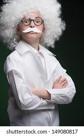 Little Einstein. Confident little boy looking like Einstein and standing isolated on black