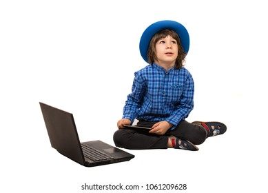 Little elegant boy  with laptop and smartphone sitting down and looking up isolated on white background