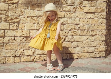 Little emotion beautiful blonde smiling girl poses. Copy space. Bright summer street photos of a little fashionista.