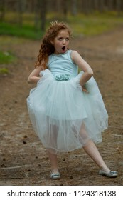 Little emotional girl in a princess dress in a summer forest, natural light