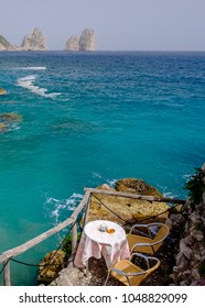 Little empty cafe table overlooking crystal turquoise sea at Marina Piccola bay, Capri, Italy.