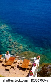 Little empty cafe with tables and chairs overlooking crystal turquoise sea at Sant Angelo, Ischia, Italy.