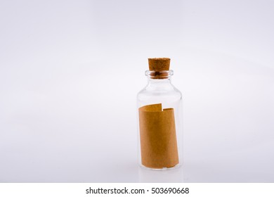 Little empty glass bottle in hand on a white background