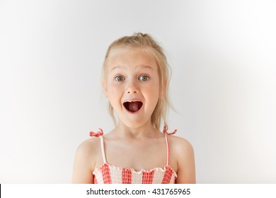 Little European girl opening mouth in surprise and raising her eyebrows with wonder. Blond child with naive glance, trustful simplicity and amazed face.