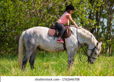 Little European girl in pink rides a white horse breed Orlov trotter at sunny day