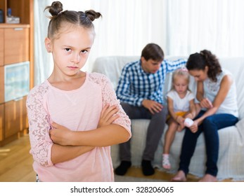 Little european girl sad because of jealous younger sister to parents. focus on girl