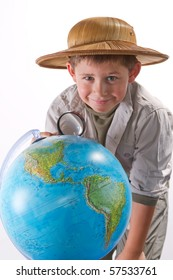 little explorer examining earth globe with magnifying glass