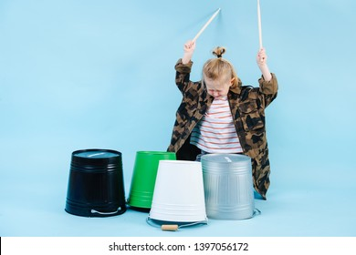 Little expressive blond boy drum music with iron and plastic buckets. Using all his force to make louder sound.