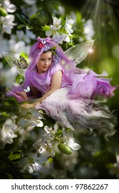 Little fairy girl on the blossom cherry branch