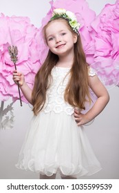 Little fairy girl in white dress on a background of flowers. Photo taken in studio