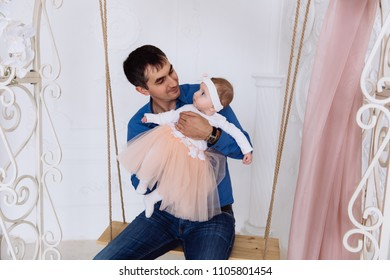 A little fairy sits on the hands of his dad. The girl in a beautiful pompous skirt looks at her father and looks at him with interest.