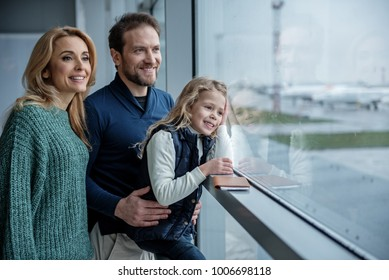 Little family looking out the window at the plane. Their faces expressing enjoyment. Copy space in right side