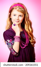 Little fashion girl in beautiful dress and beads posing over pink background.