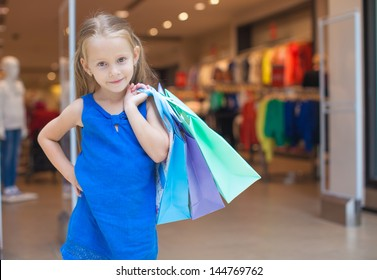 Little fashion girl with packages in a large shopping center