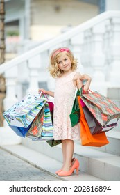 Little fashion girl with packages in a large shopping center. Pretty smiling little girl with shopping bags posing in the shop