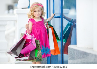 Little fashion girl with packages in a large shopping center. Pretty smiling little girl with shopping bags with thumb up sign in the shop