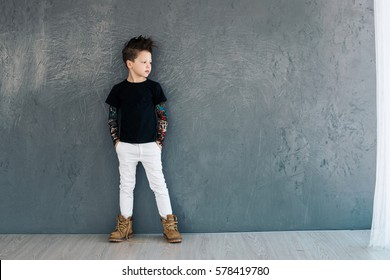 Little fashionable boy on the background of gray walls. Space for text.