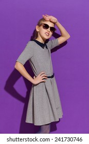 Little fashionable girl. Young girl in sunglasses posing in gray dress. Three quarter length studio shot on violet background