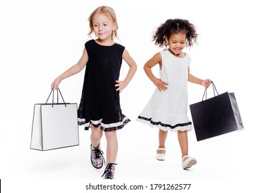 Little fashionable girls girlfriends of two different nationalities posing on a white background with bags from the store