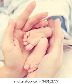 Little feet a newborn baby in hands of mum
