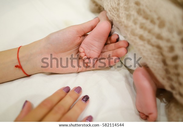 Little feet of newborn baby in mother's arms, covered warm  beige  knitted blanket which on white bed in bedroom.