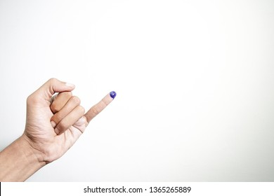 The little finger of a man's hand with blue ink patches isolated on a white background. blue ink spots from the fingers of Indonesia's presidential election (presidential election).