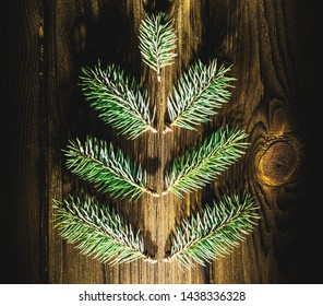 little fir tree branch in the shape of xmas tree on a wooden desk as symbol of the Happy New Year and Merry Christmas