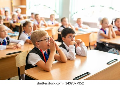 Little first-grader, girl-student goes to school on knowledge day - September First. Student of elementary school in uniform with bows posing in classroom . Russia, Krasnodar, September, 1, 2018.
