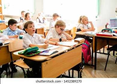 Little first-grader, girl-student goes to school on knowledge day - September First. Student of elementary school in uniform with bows posing in classroom. Russia, Krasnodar, September, 1, 2017.