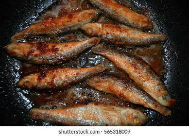 little fish is fried in a pan