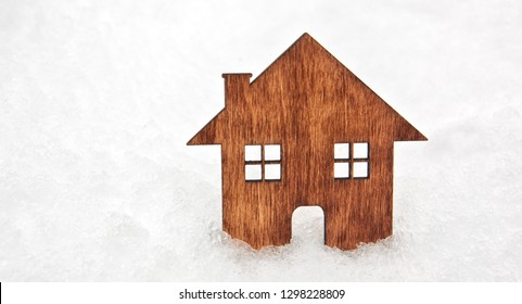 A little flat wooden house stands in the snow