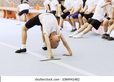 Little flexible boy showing crab posture on rubber ground of gym while having class of physical education