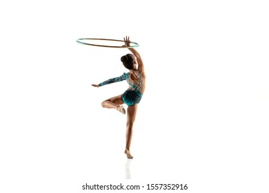 Little flexible girl isolated on white studio background. Little female model as a rhythmic gymnastics artist in bright leotard. Grace in motion, action and sport. Doing exercises with the hoop.