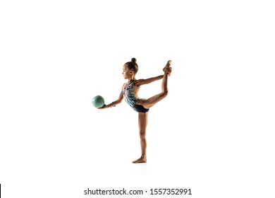 Little flexible girl isolated on white studio background. Little female model as a rhythmic gymnastics artist in bright leotard. Grace in motion, action and sport. Doing exercises with the ball.