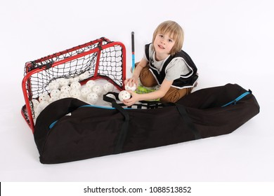 Little floorball goalkeeper boy protecting a goal