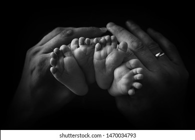 Little foot of a newborn twins on a black background close-up