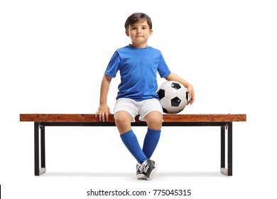 Little footballer sitting on a bench isolated on white background