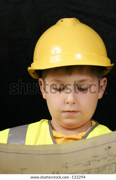 Little foreman reviews some plans.  Focus on boy, plans are oof.