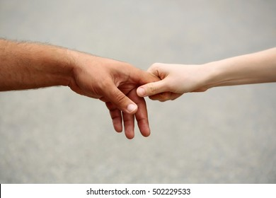 Little fragile baby hand holding fathers finger on gray background
