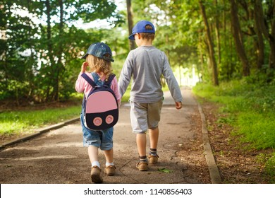 Little friends children hold hands and walk along path in park on summer day. boy and girl are walking in park outdoors along the paths. Child friendship