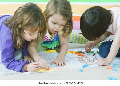 Little friends playing and drawing with crayons in kindergarten