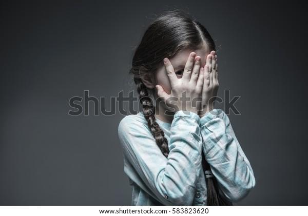 Little frightened girl peeping through fingers